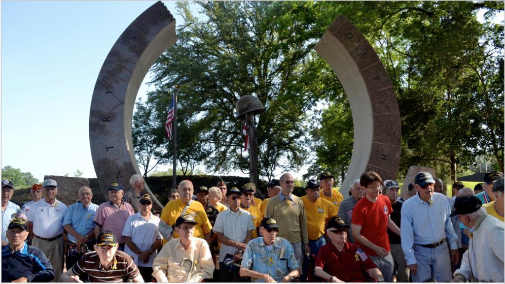 "Korean War Veterans standing in front of the Korean War Memorial ""Circle of Life"" at Cascades Parks"