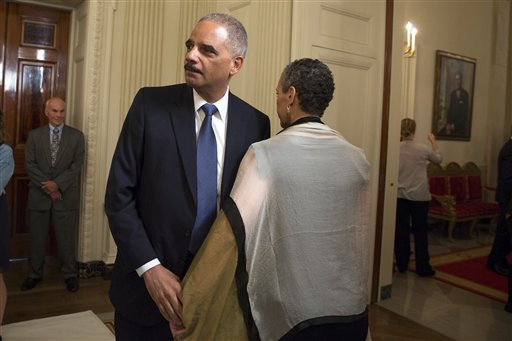 Attorney General Eric Holder, left, stands with his wife Sharon Malone after announcing his resignation in the State Dining Room of the White House, on Thursday, Sept. 25, 2014, in Washington. Holder, who served as the public face of the Obama administration's legal fight against terrorism and weighed in on issues of racial fairness, is resigning after six years on the job. He is the first black U.S. attorney general. (AP Photo/Evan Vucci)