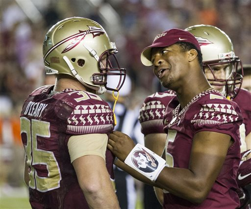 Suspended Florida State quarterback Jameis Winston, right, talks to tight end Nick O'Leary during a timeout in the second half of an NCAA college football game against Clemson in Tallahassee, Fla., Saturday, Sept. 20, 2014. Florida State won 23-17 in overtime. (AP Photo/Mark Wallheiser)