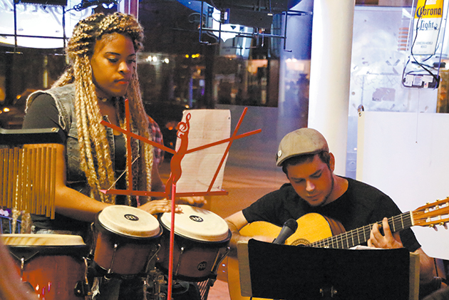 """Members of local band """"Common Situation""""  often play a variety of covers at local venues such as Tacos & Beer. Singer-songwriter and guitarist Robert Persac (right) is the band's only founding member. Percussionist Carmen Vessel (left) is currently a music major and later joined the band that has now been around for about three years."""