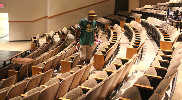 """Bruce Javery II, main stage committee head from Alpha Psi Omega, scours the aisles of the Vonnie Borden Theatre in search of any debris in preparation for the upcoming production """"Distracted."""""""
