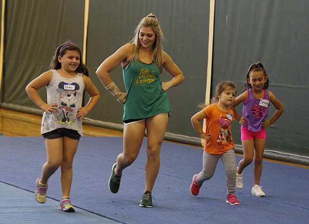 At the Lionettes and cheerleaders clinic a Lionette teaches some girls how to sassy walk for their upcoming performance at a basketball game.